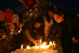 Alejanero Munoz, cq, Maria Munoz, cq, and Jessica Chavez, cq, leave lit candles at the makeshift...