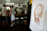 A child's drawing of a smiling Emily Keyes greets customers in the doorway of  the Cutthroat Cafe,...