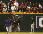 Members of the Rockies check on a fan who fell out of the bleachers trying to catch a ball during...