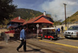 A tourist makes his way across the tracks at the Pikes Peak Cog Railway as a wildfire burns nearby...