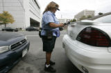 Bonnie Medina (cq) a Denver Vehicle Control Agent, writes tickets on Braodway in front of the...