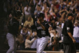 [ES0883] Seth Smith high-fives Troy Tulowitzki after Smith scored on a sac fly by Kazuo Matsui to...