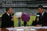 DM2588  Fans hold up signs as Drew Goodman, left, and George Frazier broadcast their pregame...