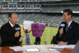 DM2596  Fans hold up signs as Drew Goodman, left, and George Frazier broadcast their pregame...