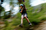 (ASPEN Colo., July 3, 2004)   Alek Kowalick, of Michigan, rides on a cable over the Roaring Fork...