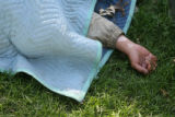 A homeless person sleeps on the park grounds on October 2, 2007. Denver wants to issue $93.4...