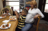 CAPTION:  Signe Newcomb, far right, sits with her son Gabe Newcomb, 4, right, and his friend...