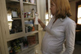 CAPTION:  Signe Newcomb looks at a figurine that she has in a shelf that houses a memorial to her...
