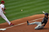 #18 Wes Helms the Phillies 3rd baseman can't stop #17 Todd Helton of the Colorado Rockies from a...
