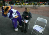 Dinger, the Colorado Rockies mascot, jokes around with Jessica Brown, as she fills out paperwork...