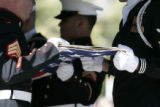 The color-guard folds the flag covering the casket of Navy Hospital Corpsman 2nd Class Charles...