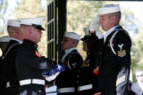 The color-guard salutes the flag covering the casket of Navy Hospital Corpsman 2nd Class Charles...