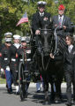 A hearse leading the color-guard  carries the casket of Navy Hospital Corpsman 2nd Class Charles...