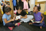 Eighth-grade volunteer Yesenia Chavez (cq), 13, reads with Jade Garcia, left, and De'Ajeca Dixon,...