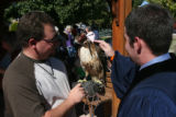 Rev. Jeremy Watson, right, lays his hand upon Shelia, a Redtail Hawk, held by Mario Nickerson, of...