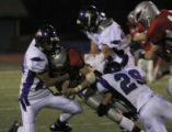 Heritage's #13 Mitch Griebel gets tackled by Douglas Co  #13 Jake Kubasta and #29 Luke Ruff in the...