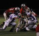 Heritages #13 Mitch Griebel eludes a sack from Douglas' #54 AJ Kortwabi and #52 Colton Hurley (r)...