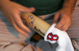 James Kalam (cq), puts a Red Sox sock back on an bat while waiting for players autographs at ...