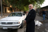 (NYT32) BAGHDAD, Iraq  -- Oct. 9, 2007 -- IRAQ-6 -- A priest stands next to a car in which two...
