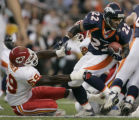 (DENVER, COLO., SEPTEMBER 12, 2004) - Denver Broncos' #22, Quentin Griffin, right, spins away from...