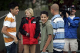 Junior Simental (cq), 16, (center) has to turn away from television cameramen and reporters to...