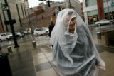 MJM075  Walking back to work after a break, Jard Horney (cq), 26, of Denver uses a trash bag with...