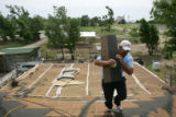 Gustavo Puga (cq) works on the roof of his mother Aurelia Puga's house in Holly, Colo., on...