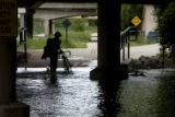 (JOE151) A bicyclist turns back after attempting to ride through a flooded section of the bike...