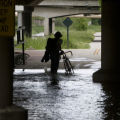 (JOE152) A bicyclist turns back after attempting to ride through a flooded section of the bike...