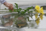 Tommie Martin, from Denver places roses on the grave of his wife's uncle, George Sturzell,  who...