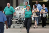 University Hospital nurses and staff along with Flight for Life staff transport a baby in an...