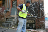 Kevin Waddy, cq, of the Denver Graffiti Task Force power washes graffiti for a brick wall, Monday...