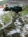 Rescue workers remove two people from a vehicle that crashed in severe weather conditions on east...