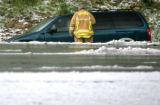 A rescue worker checks a vehicle that went off the road  in severe weather conditions on east...