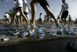 In the first mile of the run a cups are crumbled under the many feet along the route on Memorial...
