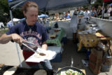 Annette Thompson (cq) makes a Greek lamb tzatziki sandwich for the Giggling Greek booth set up at...