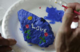 "Hospice patient Rudy Ludemann (cq) paints the word ""love"" on a rock during an arts and..."