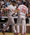 Albert Pujols is congratulated by Aaron Miles and So Tagucji  after hitting a three run homer in...