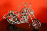 A wire sculpture of a motorcycle in his bedroom--a gift from his sister--hints at John Burr's...