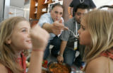 1358 Jose Andres feeds two of his daughters Carlota, 8, left, and Ines, 6, right, with four paella...