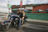Will and Suz sit upon Greg's (cq all three) Ultra Classic Harley-Davidson in front of Lincoln's...