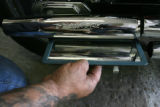 Bogart, cq, of Scotter Trash in Denver, holds a mirror to a Harley OEM performance exhaust to show...