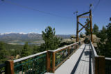 A foot bridge outside the home of Thomas Beck in Estes Park, supports three windmills that...