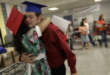 Taylor Crowley (cq), 18, hugs fellow Marshalltown High School graduate Zachary Broshar (cq), 17,...