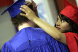 Ian Brockway (cq), 18, gets help putting on his graduation cap  from his girlfriend Anayely...