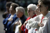 Jean Scully, right, says the Pledge of Allegiance with other members of the various military...