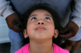 Destiny Vargas (cq), 5, looks up at her father Thomas Ramos (cq) as they take a break from...