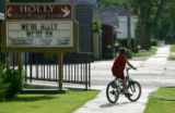"Tyler Crum (cq), 7, rides his bike past a sign that says ""We're Holly We're OK"" at the..."