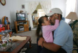 Gustavo Puga (cq), right,, gives a kiss to his daughter Noelia Puga (cq), 3, left, at his home in...