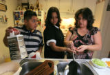 It a family thing as Bernadette 14, Joseph 11 help their mom Susan  Molina (cq) make dinner in...